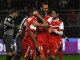 Valenciennes's Matthieu Dossevi celebrates with teammates after scoring his team's first goal against Rennes during their Ligue 1 match on March 8, 2014
