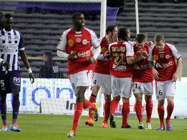 Reims' Nicolas De Preville celebrates with teammates after scoring his team's second goal against Toulouse during their Ligue 1 match on March 8, 2014