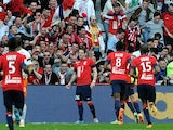 Lille's Nolan Roux celebrates with teammates in front of fans after scoring his team's second goal against Montpellier during their Ligue 1 match on March 9, 2014