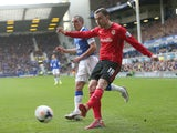 Jordan Mutch of Cardiff City shoots away from Leon Osman of Everton during the Barclays Premier League match between Everton and Cardiff City at Goodison Park on March 15, 2014
