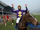 Davy Russell celebrates after riding Lord Windermere to victory in the Betfred Cheltenham Gold Cup Chase on Gold Cup day at the Cheltenham Festival at Cheltenham Racecourse on March 14, 2014