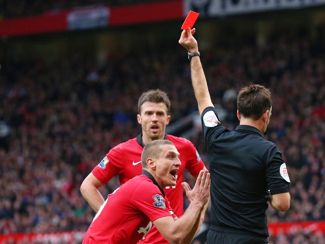 Nemanja Vidic of Manchester United is shown a red card by Referee Mark Clattenburg during the Barclays Premier League match between Manchester United and Liverpool at Old Trafford on March 16, 2014