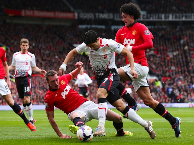 Luis Suarez is tackled by Phil Jones and Maroune Fellaini during the Barclays Premier League game between Manchester United and Liverpool at Old Trafford on March 16, 2014