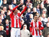 Peter Crouch and Peter Odemwingie of Stoke City celebrate as Crouch's shot deflects into the goal off of Odemwingie for their first goal during the Barclays Premier League match between Stoke City and West Ham United at Britannia Stadium on March 15, 2014