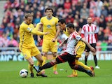 Liam Bridcutt of Sunderland clears the ball ahead of Thomas Ince of Crystal Palace during the Barclays Premier League match between Sunderland and Crystal Palace at The Stadium of Light on March 15, 2014