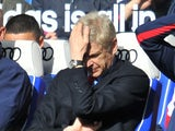 Arsenal's French manager Arsene Wenger (C) puts his hand on his head as he watches from the dug out during the English Premier League football match against Chelsea on March 22, 2014