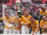 Ian Miller of Cambridge United lifts the trophy as his team celebrate during the FA Carlsberg Trophy Final 2014 at Wembley Stadium on March 23, 2014