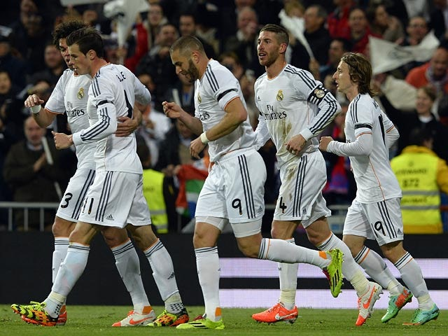 Real's Karim Benzema celebrates with teammates after scoring his team's first goal against Barcelona in the La Liga match on March 23, 2014
