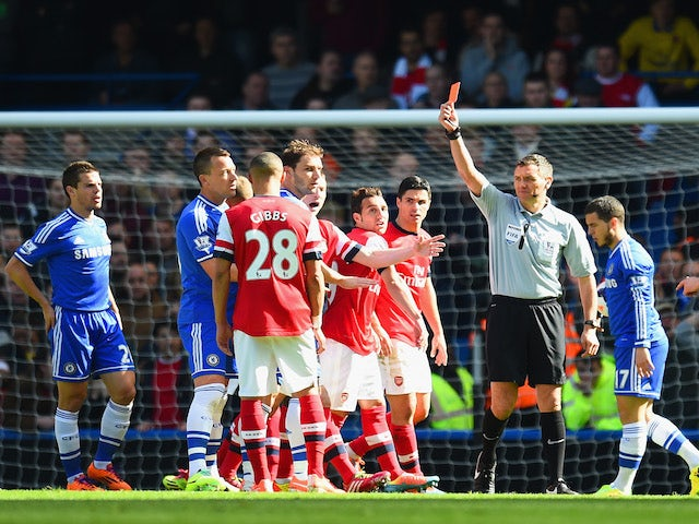 Referee Andre Marriner shows Kieran Gibbs of Arsenal a red card during the Barclays Premier League match between Chelsea and Arsenal at Stamford Bridge on March 22, 2014
