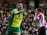 Robert Snodgrass of Norwich City celebrates scoring the opening goal as a dejected John O'Shea of Sunderland reacts during the Barclays Premier League match on March 22, 2014