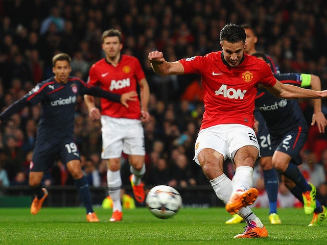 Robin van Persie of Manchester United scores the opening goal from a penalty kick during the UEFA Champions League Round of 16 second round match against Olympiacos on March 19, 2014