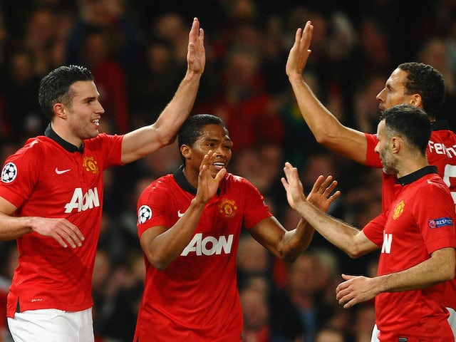Robin van Persie of Manchester United celebrates scoring the second goal with his team-mates during the UEFA Champions League Round of 16 second round match against Olympiacos on March 19, 2014