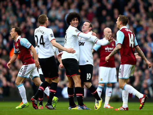 Wayne Rooney of Manchester United is congratulated by teammate Marouane Fellaini of Manchester United after scoring the opening goal against West Ham United on March 22, 2014