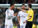 Referee Alberto Undiano Mallenco talks to Pepe (L), Cristiano Ronaldo and Xabi Alonso of Real Madrid during the La Liga match between their side and Barcelona on March 23, 2014