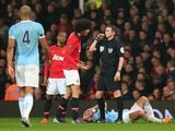 Marouane Fellaini of Manchester United is booked by Referee Michael Oliver for a challenge on Pablo Zabaleta of Manchester City during the Barclays Premier League match between Manchester United and Manchester City at Old Trafford on March 25, 2014