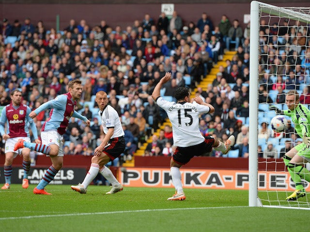 Grant Holt of Aston Villa (L) watches his effort on goal go past goalkeeper David Stockdale of Fulham during the Barclays Premier League match on April 5, 2014
