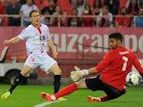Sevilla's French forward Kevin Gameiro (L) scores during the Spanish league football match Sevilla FC vs RCD Espanyol at the Ramon Sanchez Pizjuan stadium in Sevilla on April 6, 2014
