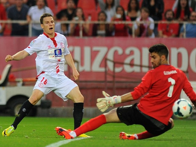 Sevilla's French forward Kevin Gameiro (L) scores during the Spanish league football match Sevilla FC vs RCD Espanyol at the Ramon Sanchez Pizjuan stadium in Sevilla on April 6, 2014