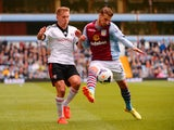 Lewis Holtby of Fulham is challenged by Joe Bennett of Aston Villa during the Barclays Premier League match between Aston Villa and Fulham at Villa Park on April 5, 2014
