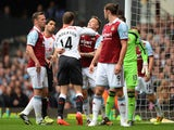 Jordan Henderson of Liverpool clashes with Matthew Taylor of West Ham during the Barclays Premier League match at Upton Park on April 6, 2014