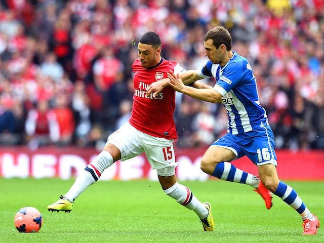 Alex Oxlade-Chamberlain of Arsenal is challenged by James McArthur of Wigan Athletic during the FA Cup Semi-Final match against Wigan Athletic on April 12, 2014