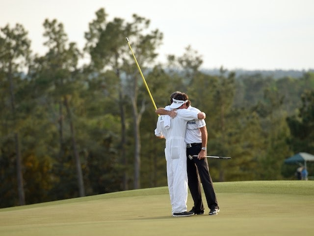 American golfer Bubba Watson celebrates with his caddy on the 18th green at Augusta National Golf Club, Georgia after winning The Masters on April 13, 2014