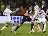 Paris' Uruguayan forward Edinson Cavani (C) vies for the ball with Lyon's French midfielder Jordan Ferri (L) and Lyon's French midfielder Maxime Gonalons during a match on April 13, 2014