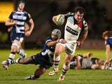 Dave Ward of Harlequins is tackled by Sam Tuitupou of Sale Sharks during the Aviva Premiership match between Sale Sharks and Harlequins at AJ Bell Stadium on April 11, 2014