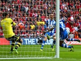 Scott Carson of Wigan Athletic makes a save from Yaya Sanogo of Arsenal during the FA Cup Semi-Final match on April 12, 2014