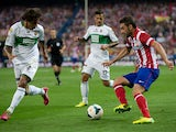 Adrian Lopez of Atletico de Madrid competes for the ball with Damian Suarez of Elche FC and his teammate Javier Marquez Moreno during the La Liga match between Club Atletico de Madrid and Elche FC at Vicente Calderon Stadium on April 18, 2014