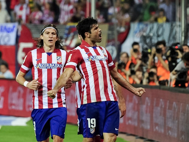 Atletico Madrid's Brazilian-born forward Diego Costa celebrates past Atletico Madrid's Brazilian defender Filipe Luis after scoring during the Spanish league football match Club Atletico de Madrid vs Elche CF at the Vicente Calderon stadium in Madrid on A