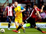 Keith Keane of Preston skips past the challenge of Marcelo Trotta of Brentford during the Sky Bet League One match between Brentford and Preston North End at Griffin Park on April 18, 2014