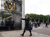 Sir Chris Hoy MBE carries the 2014 Glasgow Commonwealth Games Baton into Buckingham Palace on October 9, 2013
