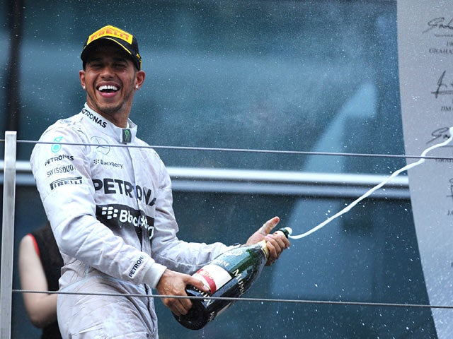 Lewis Hamilton of Mercedes celebrates with a bottle of champagne after winning the F1 Chinese Grand Prix on April 20, 2014
