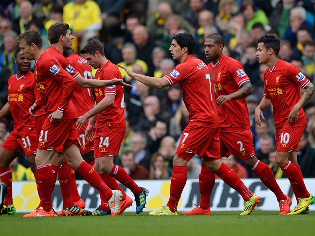 Liverpool's Luis Suarez celebrates with teammates after scoring his team's second goal against Norwich during the Premier League match on April 20, 2014