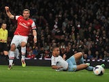 Arsenal's Polish-born German striker Lukas Podolski (L) shoots to score a goal during the English Premier League football match against West Ham United on April 15, 2014