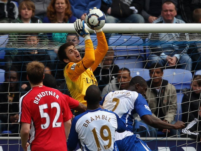 Lukasz Fabianski of Arsenal fails to collect the ball before Titus Bramble of Wigan Athletic scores the equalizing goal during the Barclays Premier League match on April 18, 2010