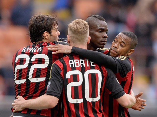 AC Milan's Mario Balotelli celebrates with teammates after scoring the opening goal against Livorno during the Serie A match on April 19, 2014