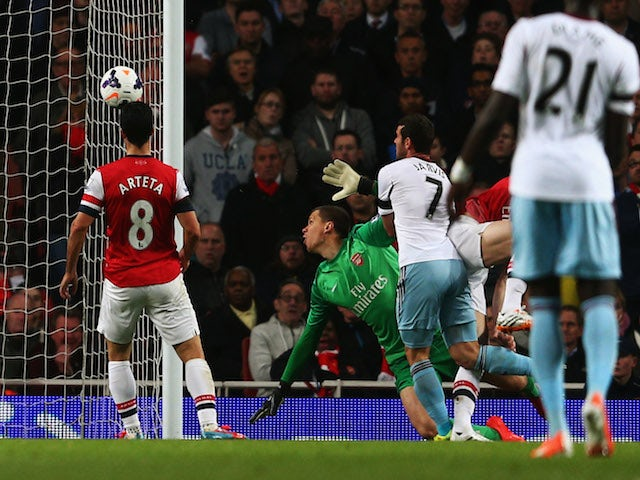 Matthew Jarvis of West Ham United (7) heads the ball past Wojciech Szczesny of Arsenal to score their first goal during the Barclays Premier League match on April 15, 2014