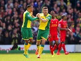 Norwich's Robert Snodgrass celebrates with teammate Martin Olsson after scoring his team's second goal against Liverpool during the Premier League match on April 20, 2014