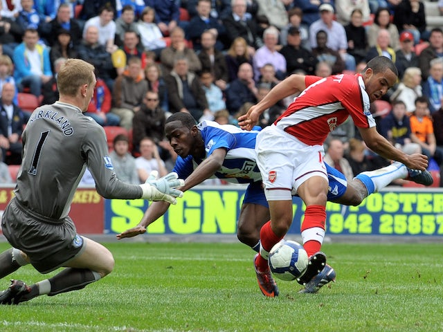 Arsenal's English forward Theo Walcott (R) scores the opening goal past Wigan Athletic's English goalkeeper Chris Kirkland (L) during the English Premier league football match on April 18, 2010