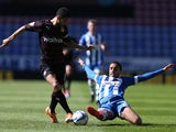 James Perch of Wigan Athletic tackles Jobi McAnuff of Reading during the Sky Bet Championship match between Wigan Athletic and Reading at DW Stadium on April 18, 2014