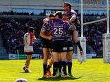 Joe Burgess of Wigan celebrates with team-mates after scoring a try during the Super League match between St Helens and Wigan Warriors at Langtree Park on April 18, 2014