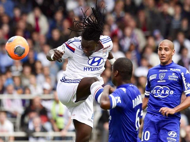 Lyon's French forward Bafetimbi Gomis (L) heads the ball and scores despite Bastia's Ivory Coast midfielder Romaric N Dri Koffi (C) and Bastia's Tunisian midfielder Wahbi Khazri during a match on April 27, 2014