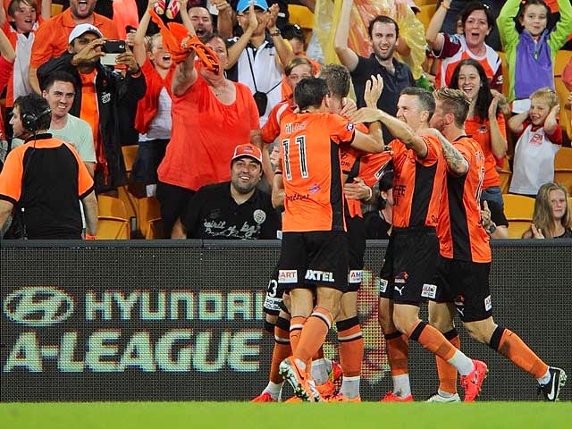 Brisbane Roar's Besart Berisha is congratulated by teammates in front of fans after scoring the opening goal against Melbourne Victory during the A-League semi-final match on April 27, 2014