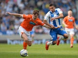 Andrew Halliday of Blackpool holds off a challenge from Jesse Lingard of Brighton during the Sky Bet Championship match between Brighton & Hove Albion and Blackpool at Amex Stadium on April 21, 2014