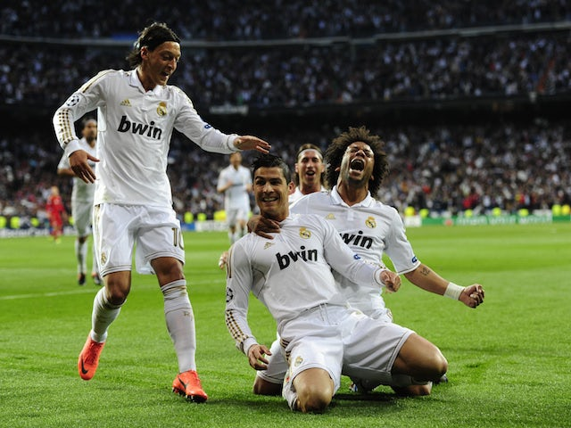 Real Madrid's Portuguese forward Cristiano Ronaldo (C) celebrates with Real Madrid's Brazilian defender Marcelo (R) and Real Madrid's German midfielder Mesut Ozil after scoring against Bayern on April 25, 2012