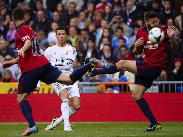 Real Madrid's Portuguese forward Cristiano Ronaldo (C) scores during the Spanish league football match Real Madrid CF vs CA Osasuna at the Santiago Bernabeu stadium in Madrid on April 26, 2014