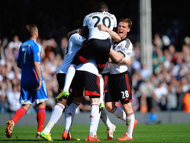 Fulham's Fernando Amorebieta is mobbed by teammates after scoring his team's second goal against Hull during the Premier League match on April 26, 2014
