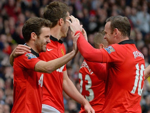 Manchester United players Juan Mata (L) and Wayne Rooney (R) celebrate after Mata scored the third goal against Norwich City at Old Trafford on April 26, 2014